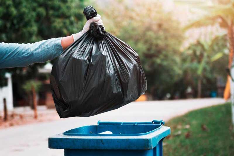 Photographie d'un sac déposé dans une poubelle